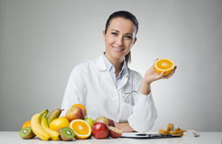 Dietician holding an orange. Smiling dietician sitting at desk and holding an orange stock image