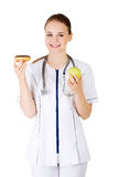 Dietician holding sweet doughnut and fresh healthy green apple. Royalty Free Stock Photos