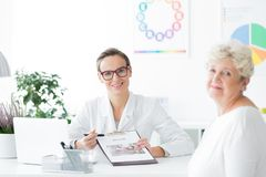 Dietician looking at camera. Dietician in glasses showing a clipboard with diet plan looking ahead at the camera royalty free stock images