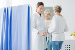 Dietician measuring patient`s body circuit. Dietician measuring body circuit of patient with overweight stock image