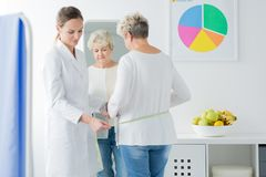Dietician measuring a woman. A dietician measuring a women during a follow-up appointment royalty free stock photography