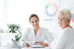 Dietician in office with patient. Young dietician sitting by the desk in her office with a senior patient and looking directly at the camera stock images