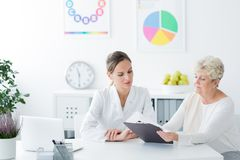 Dietician showing personalized diet plan. To diabetic patient in the health center royalty free stock photography