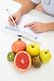 Dietician writing prescription with fruits on desk Stock Photos
