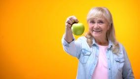 Усмехаясь дама пенсионера вегетарианская показывая сочное зеленое яблоко, натуральные продукты, dieting стоковые изображения