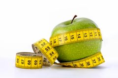 Dieting. A green apple with measuring tape, isolated on a white background royalty free stock photos