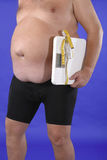 Dieting. Fat man with bathroom scale and tape measure as symbol for dieting Royalty Free Stock Image