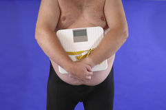 Dieting. Fat man with bathroom scale and tape measure as symbol for dieting Royalty Free Stock Images