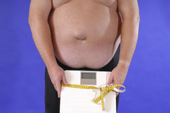 Dieting. Fat man with bathroom scale and tape measure as symbol for dieting Royalty Free Stock Photography