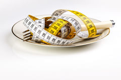 Dieting. Fork with measuring tape as a symbol of disciplined dieting and weight reduction Stock Photo