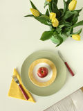 Dieting. Place setting with red apple on colorful plates, fork, knife, paper napkin and a bunch of yellow tulips. View from above Stock Image
