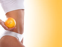 Dieting concept, Beautiful belly and a fruit on white Royalty Free Stock Photos