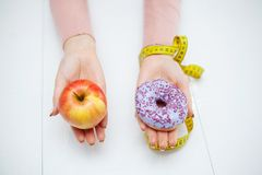 Dieting concept, beautiful young woman choosing between healthy food and junk food.  stock images