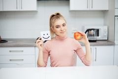 Dieting concept, beautiful young woman choosing between healthy food and junk food.  stock image