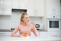 Dieting concept, beautiful young woman choosing between healthy food and junk food.  royalty free stock images