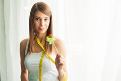 Dieting concept, beautiful young woman choosing between healthy food and junk food.  royalty free stock photography