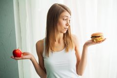 Dieting concept, beautiful young woman choosing between healthy food and junk food royalty free stock photography