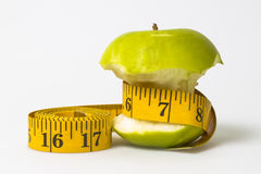 Dieting concept Green apple with measuring tape Royalty Free Stock Image