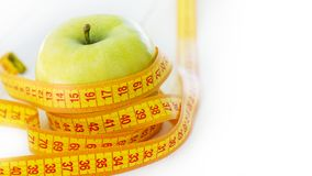 Dieting concept. Green apple with measuring tape. Green apples measured the meter, sports apple.  royalty free stock images