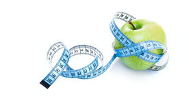 Dieting concept green apple with measuring tape Royalty Free Stock Photo