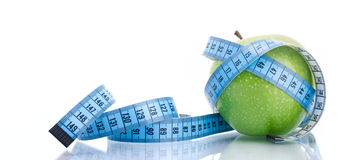 Dieting concept green apple with measuring tape Stock Images
