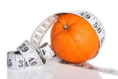 Dieting concept, orange with measuring tape Royalty Free Stock Photos