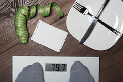 Dieting concept with scales on the wooden floor Stock Image