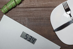 Dieting concept with scales on wooden floor Stock Images