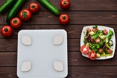Dieting and control calories for good health concept. salad. smart weight scales. veggies on board. Fitness concept stock image