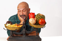 Dieting discipline. Dieting man anxiously looking at what he should not eat Royalty Free Stock Image