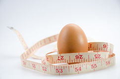 Dieting  egg. Weight loss with measuring tape on white Royalty Free Stock Photos