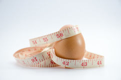Dieting  egg. Weight loss with measuring tape on white Stock Photo