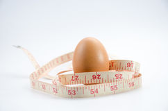 Dieting  egg. Weight loss with measuring tape on white Stock Photography