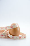 Dieting  egg. Weight loss with measuring tape on white Royalty Free Stock Photo