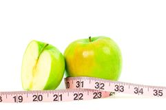 Dieting. Fresh green apple and measuring tape on white background. Fresh green apple and measuring tape on white background. Dieting and Healthy lifestyle stock images