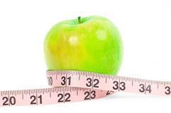 Dieting. Fresh green apple and measuring tape on white background. Fresh green apple and measuring tape on white background. Dieting and Healthy lifestyle royalty free stock image