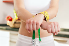 Dieting gone wild - Woman handcuffed. Woman handcuffed by a tape measure - symbol for eating disorder Stock Images