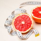 Dieting. Grapefruit with measuring tape Royalty Free Stock Photos