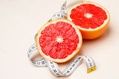 Dieting. Grapefruit with measuring tape Stock Photos