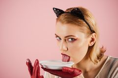 Dieting and health. Girl in kitten ears and red gloves with yoghurt on pink background. cat woman lick milk from. Plate. Food and drink. Cat woman eat sour royalty free stock photos