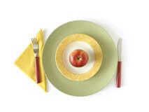 Dieting - healthy eating. Informal place setting with a red apple on colorful plates, fork, knife and paper napkins. View from above, isolated on white with soft Stock Photos