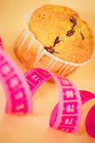 Dieting, healthy lifestyle or eating cakes?. Still-life of pink measuring tape and muffin to depict hesitation between healthy lifestyle/dieting and cakes Stock Photos