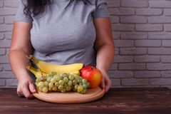 Dieting, healthy low calorie food, weight losing, weight control. Concept. Overweight woman with a dish of fruits. Useful sweets royalty free stock image
