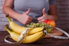 Dieting, healthy low calorie food, weight losing, weight control. Concept. Overweight woman showing thumbs up gesture, measuring tape and fruits on the dish stock photography