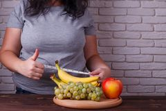Dieting, healthy low calorie food, weight losing, weight control. Concept. Overweight woman with a dish of fruits and measuring tape on her waist showing thumb stock photography