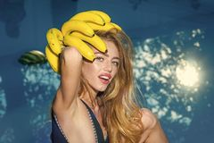 Dieting and healthy organic food, vegetarian. Vitamin in banana at girl near water. Woman relax in spa luxury swimming. Pool. woman with tropical fruit in pool stock photo