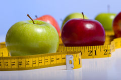 Dieting Items. Several varieties of fresh apples on a blue background with a tape measure. Dieting and healthy eating concept. Includes copy space royalty free stock photo