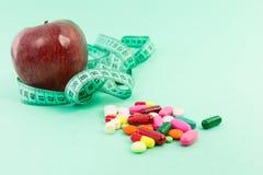 Dieting pojęcie z naturalnym jabłkiem, pomiarową taśmą i pigułkami, obraz stock