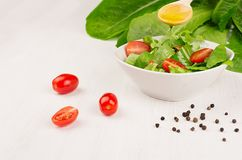 Dieting raw healthy food - fresh green salad with tomatoes, pepper and olive oil on soft white wood board, closeup, copy space. Royalty Free Stock Image