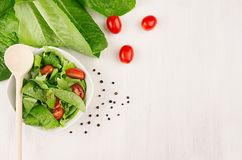Dieting raw healthy food - fresh green salad with tomatoes, pepper on soft white wood board, top view, copy space. Stock Photos
